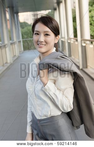 Happy smiling business woman of Asian put coat on shoulder go off work.