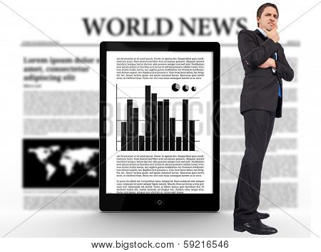Thinking businessman touching chin against digital tablet with graph