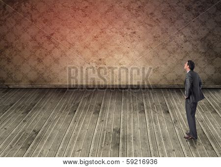 Smiling businessman with hands on hips against grimy room