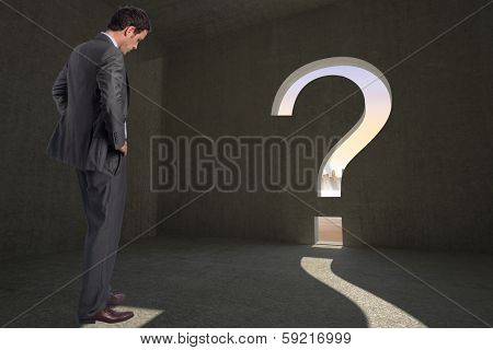 Businessman with hands on hips against question mark door in dark room