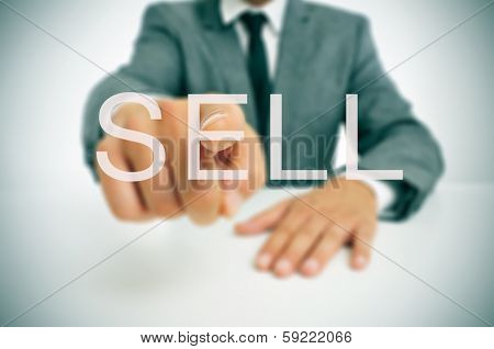 businessman sitting in a desk pointing the word sell written in the foreground