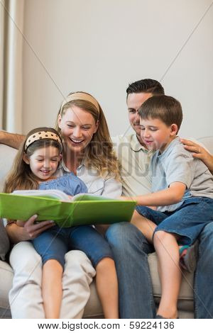 Family watching photo album together while sitting on sofa at home