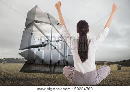 Businesswoman sitting cross legged cheering against landscape with bales of straw