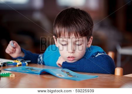 Concentrated child reading a manual