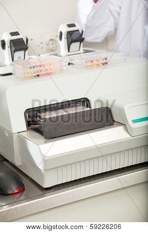 Microplates with biological samples on analyzer in laboratory