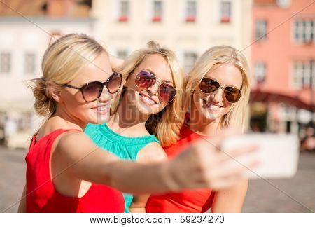 holidays, tourism and modern technology concept - smiling girls taking picture with smartphone camera in the city