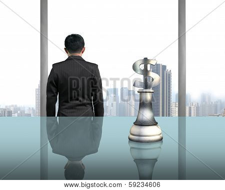 Rear View Businessman With Money Symbol Piece On Table