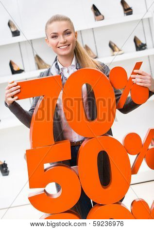 Woman showing the percentage of sales on high heeled shoes in the shopping center against the window case with pumps