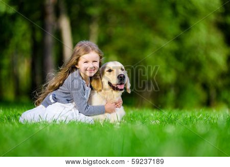 Little girl sitting on the grass with golden retriever in the summer park