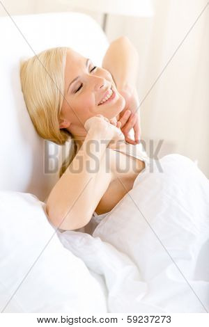 Girl stretches herself lying in bed in the morning at weekend