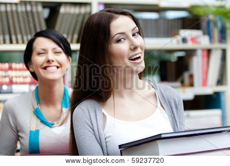 Two laughing girlfriends carry piles of books at the library