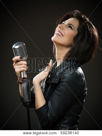 Half-length portrait of female rock musician wearing black jacket and keeping mic on grey background. Concept of music and rave