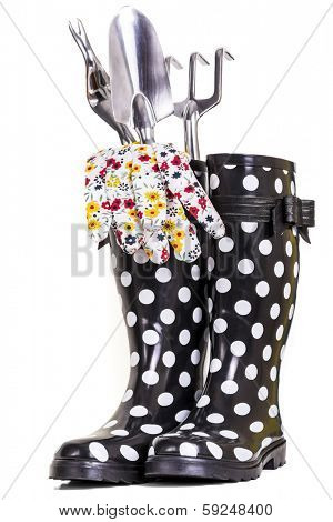 Gardening tools, gloves and rubber boots isolated on white.