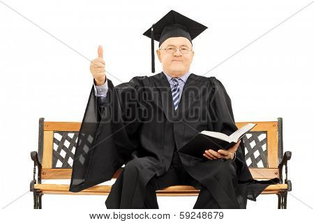 Mature man in graduation gown seated on wooden bench holding a book and giving thumb up isolated on white background