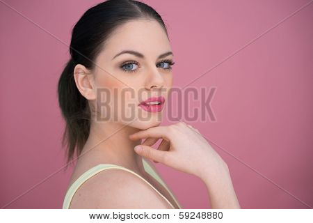 Pretty young woman with her brunette hair in a pony tail giving the camera a speculative look, over a pink background
