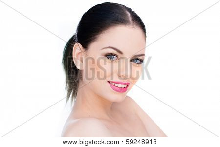 Attractive naked young brunette woman with a lovely smile and her hair tied up in a ponytail standing sideways looking at the camera, isolated on white