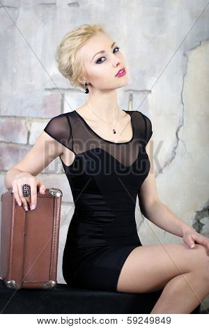 Young beautiful blond woman in a black dress smiling and holding her hand on a valise
