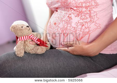 Pregnant woman with teddy bear.