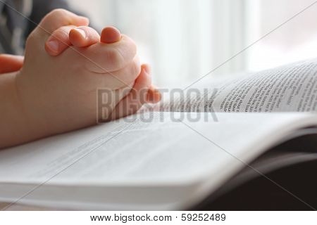Young Child's Hands Praying On Holy Bible