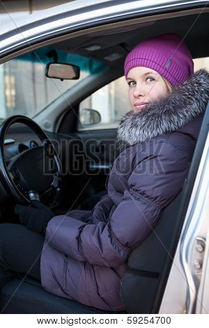 Attractive Young Woman In Winter Clothes Sitting In Car