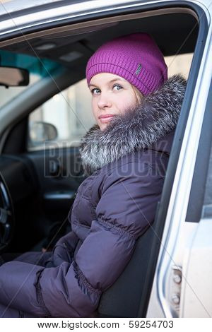 Portrait Of Attractive Young Woman In Winter Clothes In Car