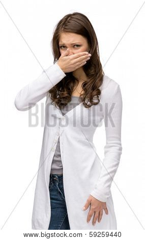 Portrait of girl covering her nose, isolated on white. Concept of stink and disgust