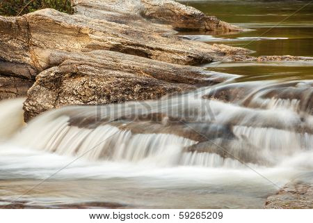 Water stream running over the rocks in the fores
