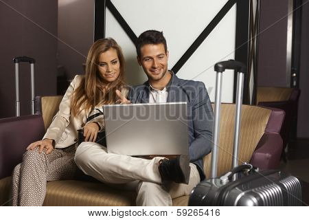 Young couple sitting on sofa at hotel lobby upon arrival, using laptop computer, smiling happy.