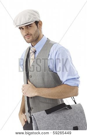 Portrait of young man holding shoulder bag wearing hat.