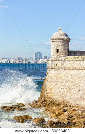 Detail of the castle of  El Morro with the skyline of Havana in the background