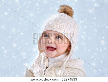 Portrait of cute little baby girl wearing warm stylish hat isolated on blue snowy background, snow falling, winter season, happy child concept