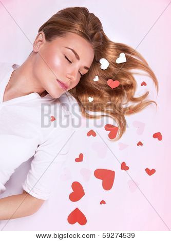 Romantic fashion model lying down on the floor with closed eyes decorated with many little red hearts, dreaming about love, Valentine day concept