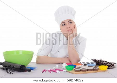 Attractive Bored Female Confectioner In Cook Uniform Sitting At The Kitchen