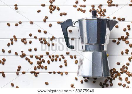 top view of coffee maker with coffee beans on white wooden background