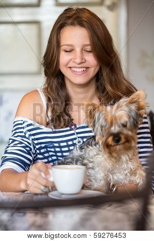 Happy smiling teenager  girl holding little dog at coffee