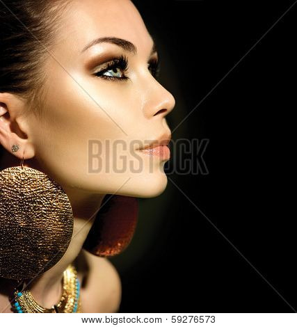 Fashion Woman Profile Portrait isolated on black. Golden Jewels. Trendy Makeup. Smoky eyes make up. Gold Jewellery. Accessories