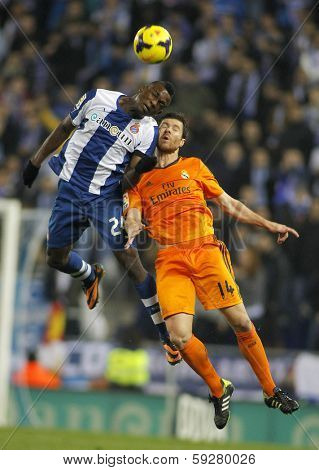 BARCELONA - JAN, 12: Xabi Alonso(R) of Real Madrid vies with Jhon Cordoba(L) of RCD Espanyol during the Spanish League match at the Estadi Cornella on January 12, 2014 in Barcelona, Spain