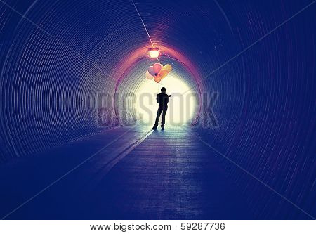 a girl at the end of a tunnel holding balloons done with an  instagram vintage retro filter