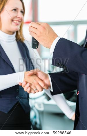 Seller or car salesman and customer in dealership, they shaking hands, hands over the car keys and seal the purchase of the auto or new car