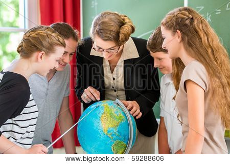 Students or pupils having group work while geography lesson and the teacher test or educate them in school or class