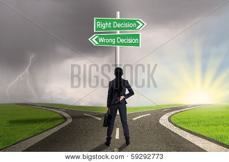 Businesswoman Looking At Sign Of Right Vs Wrong Decision