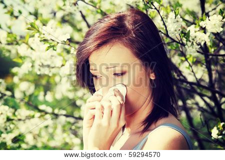 Young woman standing among blossom trees during sunny day  and wiping her nose. Girl with runny nose, having allergy and holding a tissue next to her face.