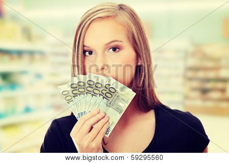 Young woman is holding euro bills and covering mouth. In shoop.