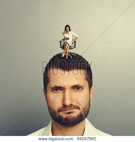 angry small woman screaming at discontented man over grey background