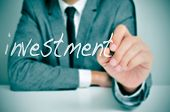 picture of enterprise  - businessman sitting in a desk writing the word investment in the foreground - JPG