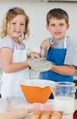 foto of flour sifter  - Portrait of cute children baking cookies together in kitchen - JPG