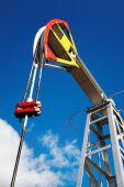 foto of nonrenewable  - Oil pump jack against blue sky background - JPG