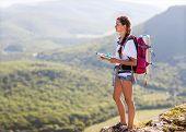 Young, Beautiful Girl With A Backpack On Her Back, Studying A Map While Standing On The Plateau. In