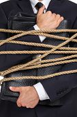 stock photo of slavery  - Close up of businessman handing briefcase who tied with the rope - JPG