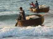 stock photo of coracle  - Fishermen coming ashore in Coracles Mui Ne Vietnam - JPG